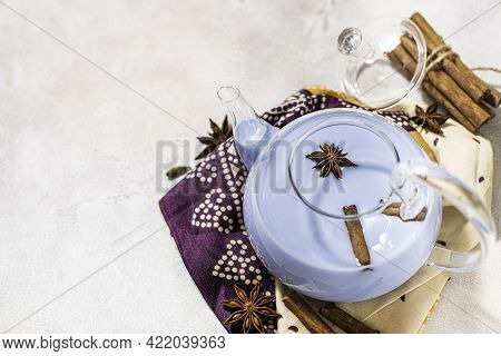 Blue Tea Masala Tea In A Glass Teapot. Indian Masala Tea Flavored With Milk And Spices.