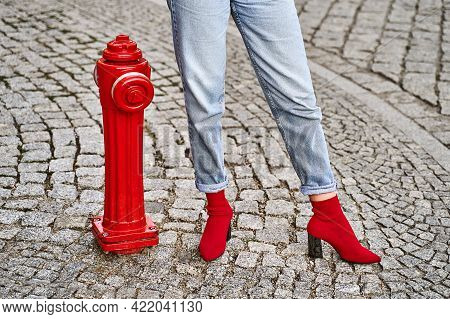 Woman Legs In Red Knitted Fabric Block Heel Sock Shoes And Blue Denim Jeans Pants Near Red Street Fi