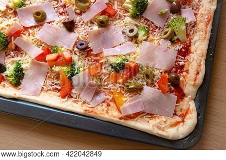 Raw Homemade Pizza With Ingredients On A Baking Tray