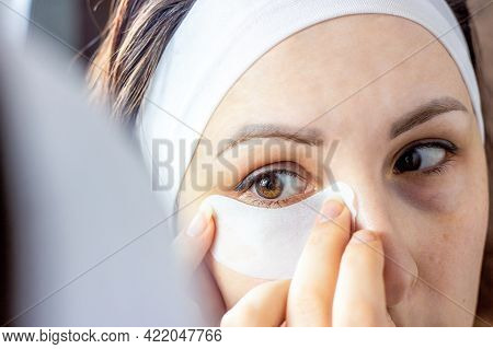 Young Caucasian Woman Applying Eye Patch Mask On Her Eyelid To Avoid Wrinkles Looking In The Mirror.