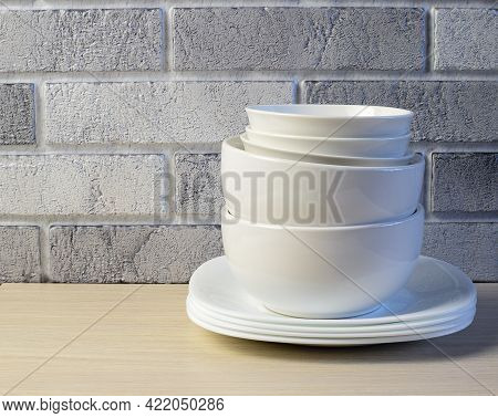 White Crockery On The Background Of A Light Brick Wall. Space For Text.