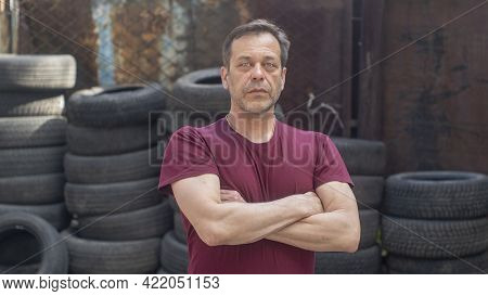 Portrait Of A Man With A Strong Build Of 45-50 Years Old Against The Background Of Old Car Tires And