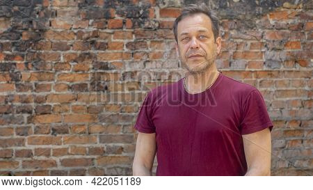 Portrait Of A Serious Elderly Man With A Strong Build Of 45-50 Years Old In A T-shirt On The Backgro