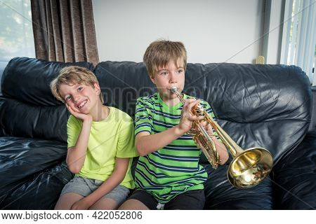 Two Kids Sitting On A Sofa.  One Is Playing A Trumpet And The Other Child Is Listening And Smiling.