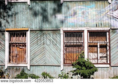 A Dilapidated Wooden Abandoned House. Old Building. Uninhabited House. The Grating On The Broken Win