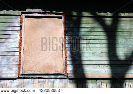 A Dilapidated Wooden Abandoned House. Old Building. Uninhabited House. A Boarded-up Window.