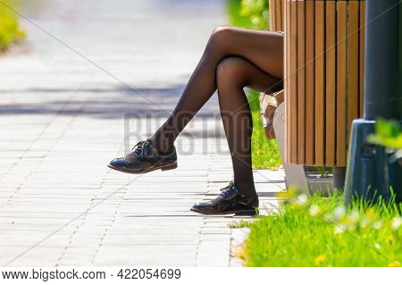 The Legs Of A Girl In Dark Tights, Who Sits On A Park Bench Against The Background Of Green Grass An