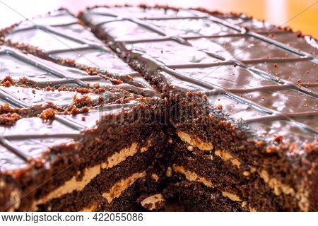 Chocolate Cake With A Cream Layer. Cut Into Pieces. Several Pieces Are Missing. Front View From Abov