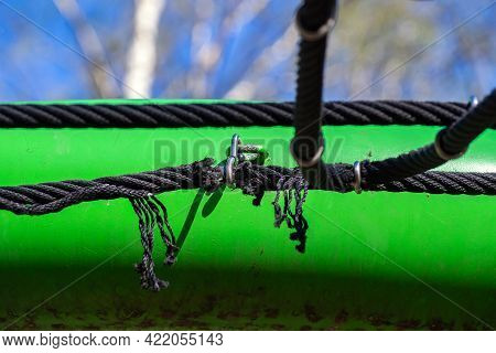The Black Synthetic Rope On The Playground Was Frayed At The Point Of Attachment To The Metal Pipe.