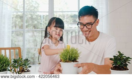 Happy Cheerful Asian Family Dad And Daughter Watering Plant In Gardening Near Window At House. Self-