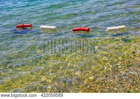 Sunny Summer Day. Shallow Water, String Of Red And White Buoys On Water. Beach Vacation Concept