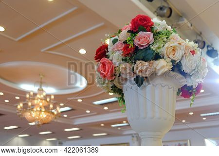 Colorful Plastic Rose Flowers In Roman Tuscan Marble Planter With Background Of Ceiling And Beautifu