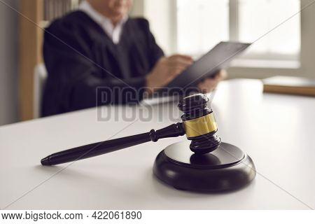 Close Up Of A Dark Brown Judge Gavel On A Table Against The Backdrop Of A Judge Reading A Verdict.