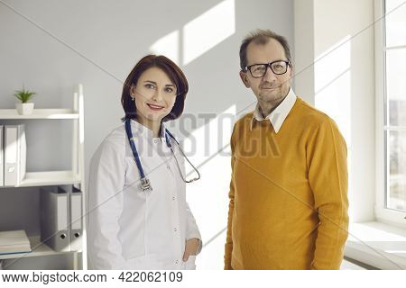 Portrait Of A Female Doctor And Senior Male Patient In A Bright Office Of A Modern Private Clinic.