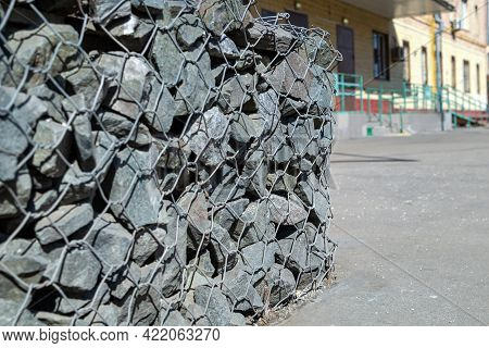 Gabion Construction With Small Gray Stones On The Background Of An Urban View