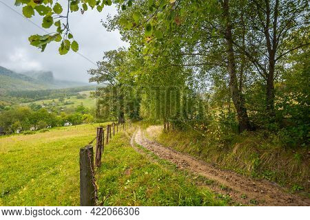 Rural Dirt Road To Village. Autumnal Countryside Of Carpathian Mountains. Rainy Weather. Fence Along