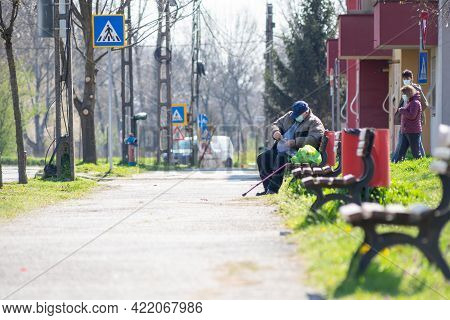 Timisoara, Romania - April 05, 2021: Man Sitting On A Bench In The Street. Two People Walking. Real