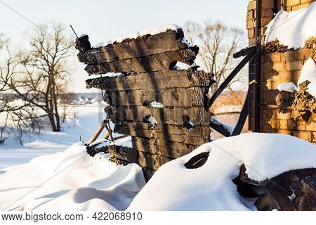 Remains Of A Charred Wooden Wall Of A Burnt House, The Ruins Of A Building After A Fire Covered With