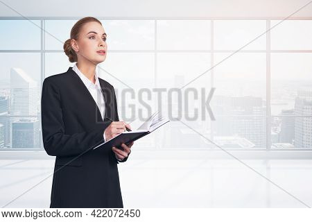 Office Woman In Black Suit, Carefully Listening With Notebook In Hands, Skyscrapers On Background. C