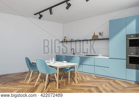 Corner Of Modern Dining Room With White Walls, Wooden Floor, Blue Counters And Dining Table With Blu