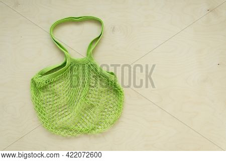 Green Mesh Tote Bag On Wooden Background. Tote Bag On Wooden Background With Copy Space. Flat Lay. T