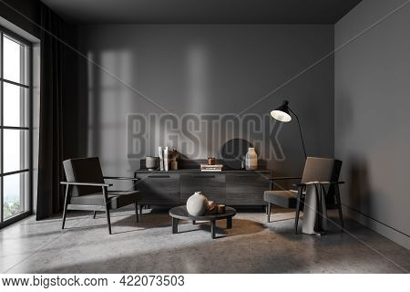 Modern Living Room Interior With Two Chairs And Commode With Art Books On Concrete Floor, Lamp And W