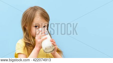 World Milk Day. Cute Little Girl Drinks White Milk From Transparent Glass On Blue Background. Baby C