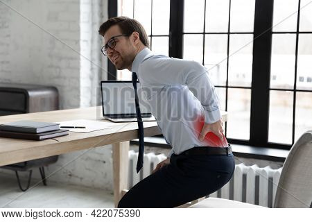 Upset Office Manager Touching Painful Back And Standing Up