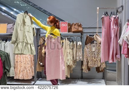 Caucasian Woman Chooses Fashionable Clothes For The Spring Summer Season In A Large Store. The Girl