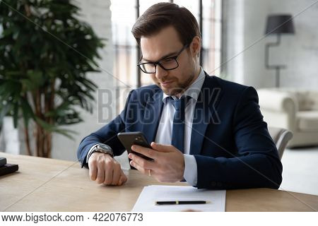 Punctual Business Leader Checking Time On Wrist Watch And Smartphone