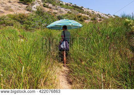 Stara Baska, Croatia - July, 22: Woman Walks Along The Path Grass Protecting Herself From The Sun Wi