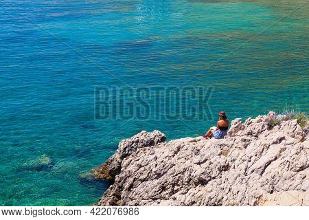 Stara Baska, Croatia - July, 22: Girl Reading A Book Sitting On The Rock Next To The Sea On July 22,