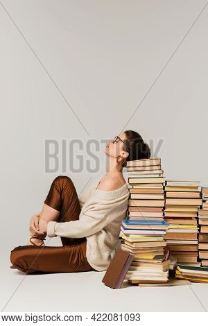 Side View Of Young Woman In Glasses And Sweater Leaning On Stack Of Books On White.