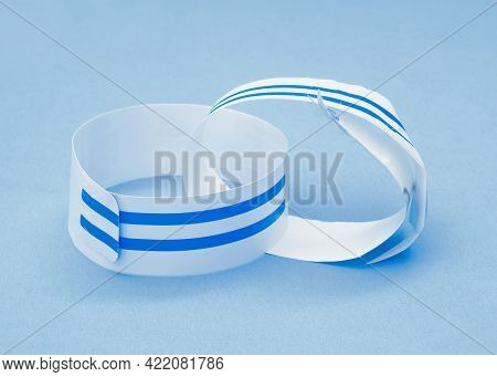 Discarded Hospital Wristbands On Light Blue Background