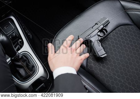 Top View Of Bodyguard Reaching Gun On Seat Of Modern Automobile.