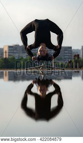 Flexible And Fit Girl Bending Her Back Upside Down With Reflection In The Water. Concept Of Individu