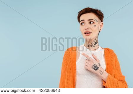 Amazed Young Tattooed Woman In Orange Cardigan Pointing Away With Finger Isolated On Blue.