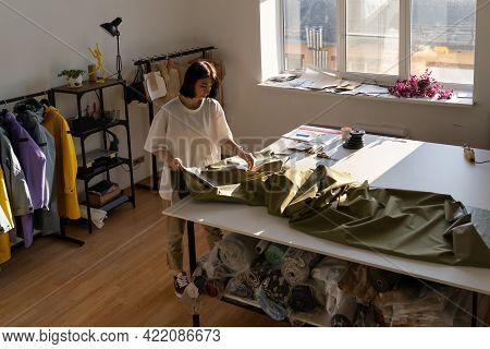 Female Clothes Designer Working With Fabric In Modern Atelier. Casual Tailor With Big Skein Of Cloth