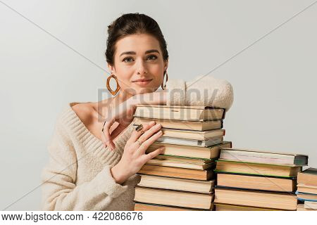 Pleased Young Woman In Earrings Leaning On Stack Of Books Isolated On White.