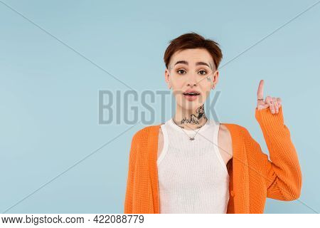 Amazed Young Tattooed Woman In Orange Cardigan Pointing Up With Finger Isolated On Blue.