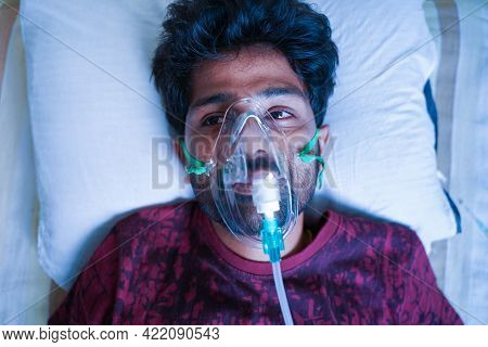 Top View Of Young Man Breathing On Ventilator Or Oxygen Concentrator Mask At Hospital Due Coronaviru