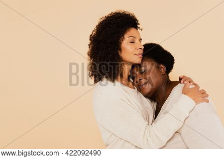 African American Adult Daughter Hugging Middle Aged Mother With Closed Eyes Isolated On Beige.