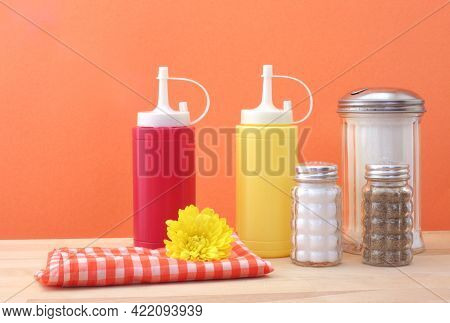 Diner Counter With Ketchup, Mustard, Sugar, Sat, Pepper And Napkin With Flower