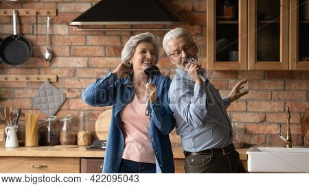 Happy Middle Aged Spouses Dancing Singing In Kitchen