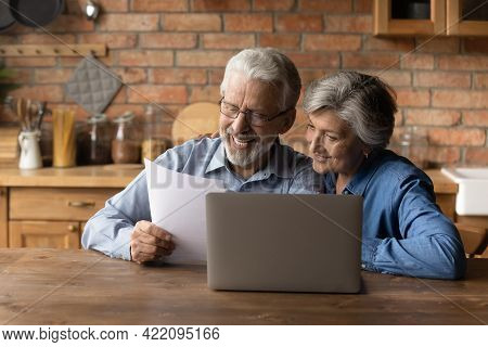 Happy Middle Aged Couple Reading Good News In Document