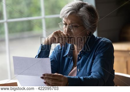 Middle Aged Female Reading Letter Looking Concerned