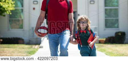 Parent Take Child To School. Pupil Of Primary School Go Study With Backpack Outdoors. Father And Son