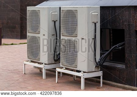 Two Double Condensing Units Of Air Conditioner On The Ground Level Near Granite Building Wall
