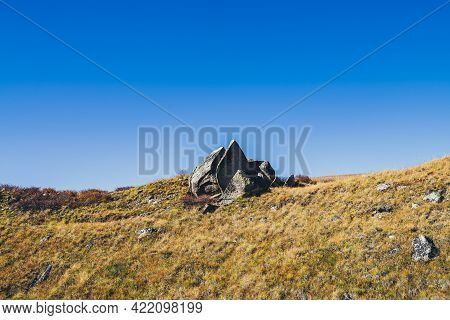 Minimal Autumn Landscape With Pointy Shattered Stone On Orange Hill In Sunlight Under Blue Clear Sky