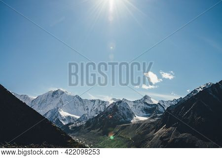 Alpine Landscape With High Snowy Mountain With Peaked Top Under Cirrus Clouds In Sun With Lens Flare